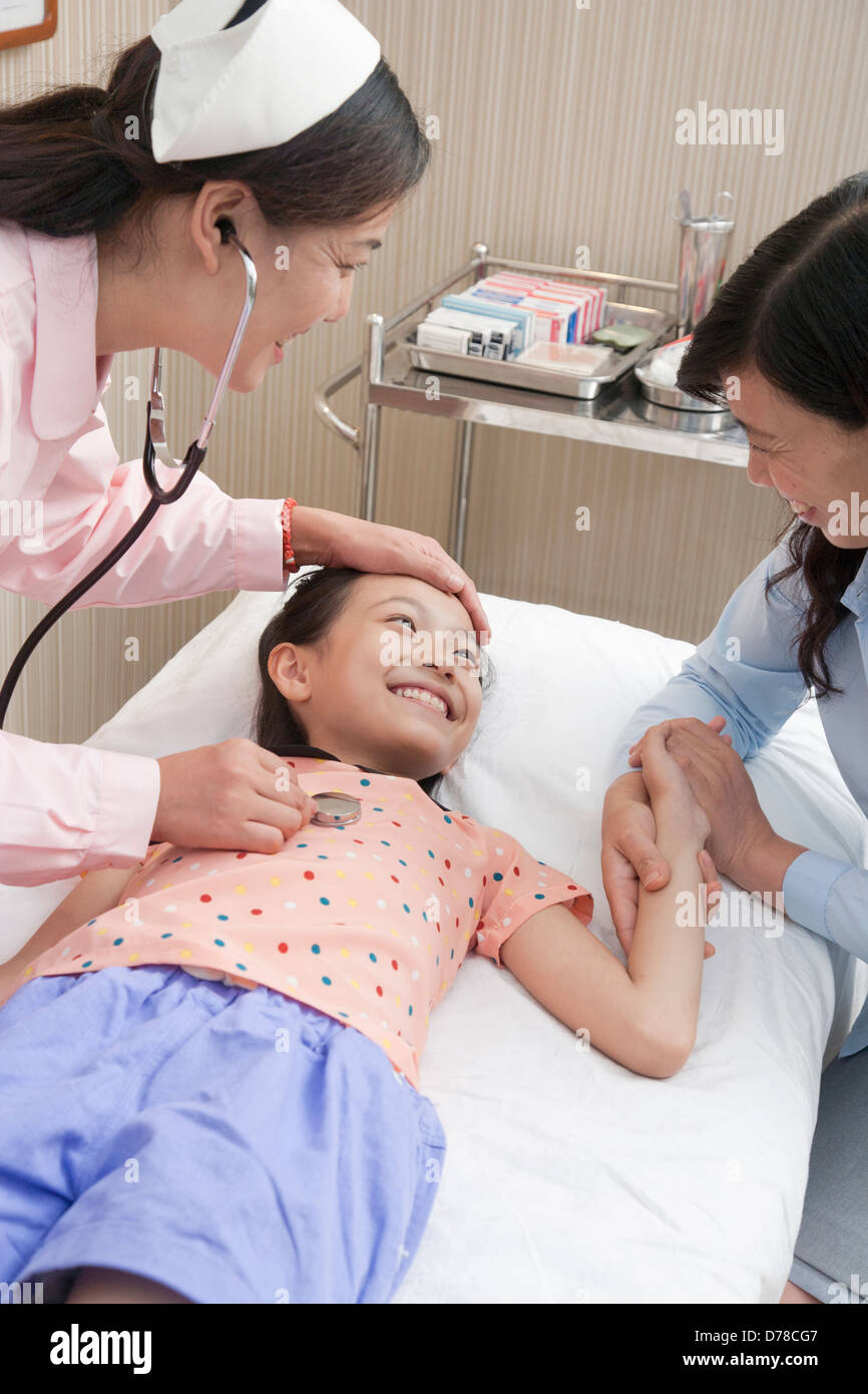 Doctor Listens to Little Girl's Heartbeat - Stock Image