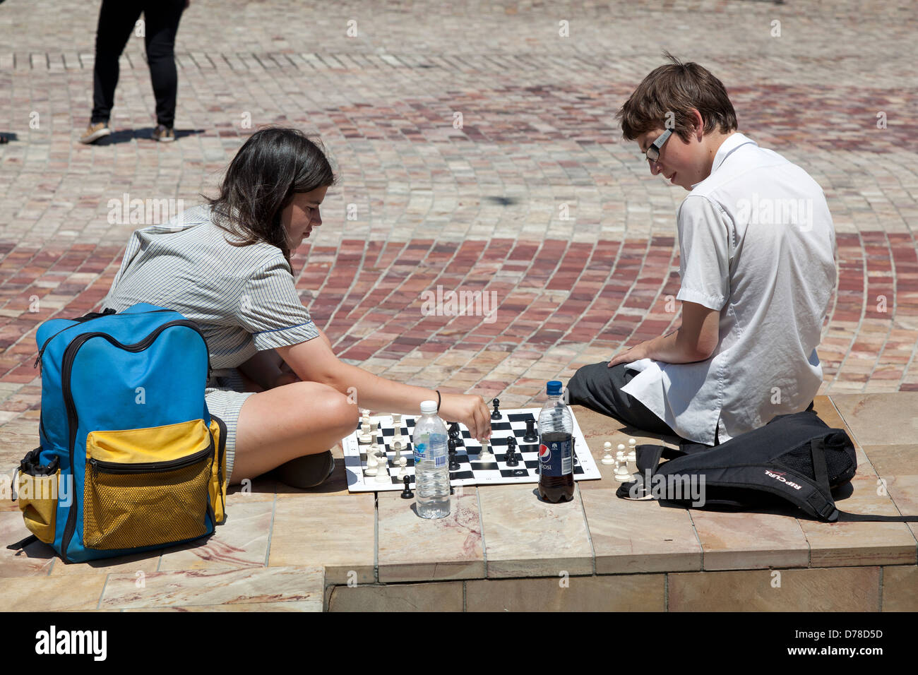 Teenagers playing chess at Federation Square, Victoria, Australia - Stock Image