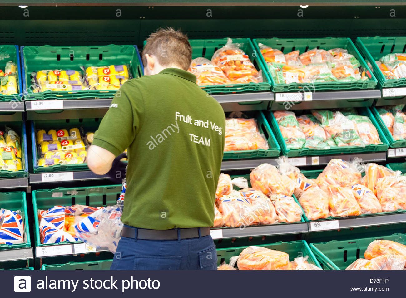 Young man stacking shelves in a Tesco store, UK. - Stock Image