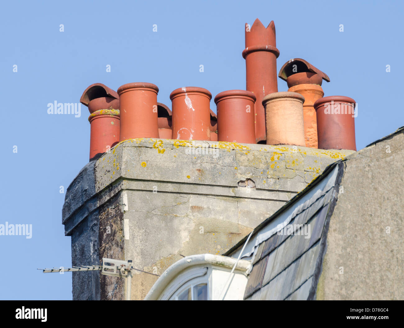 Chimney with several different old style chimney pots protruding. - Stock Image