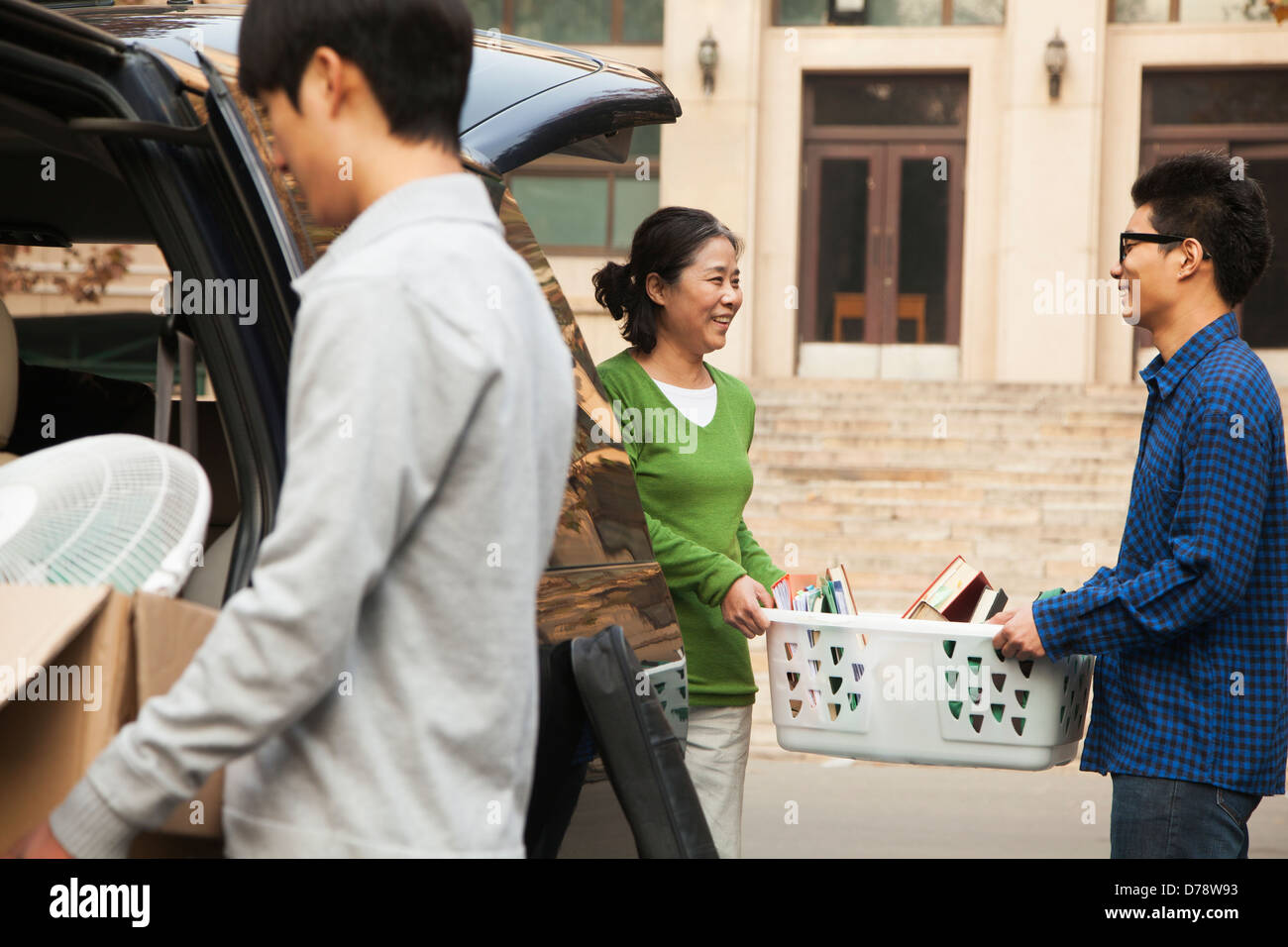 Family moving their son into dormitory on college campus - Stock Image