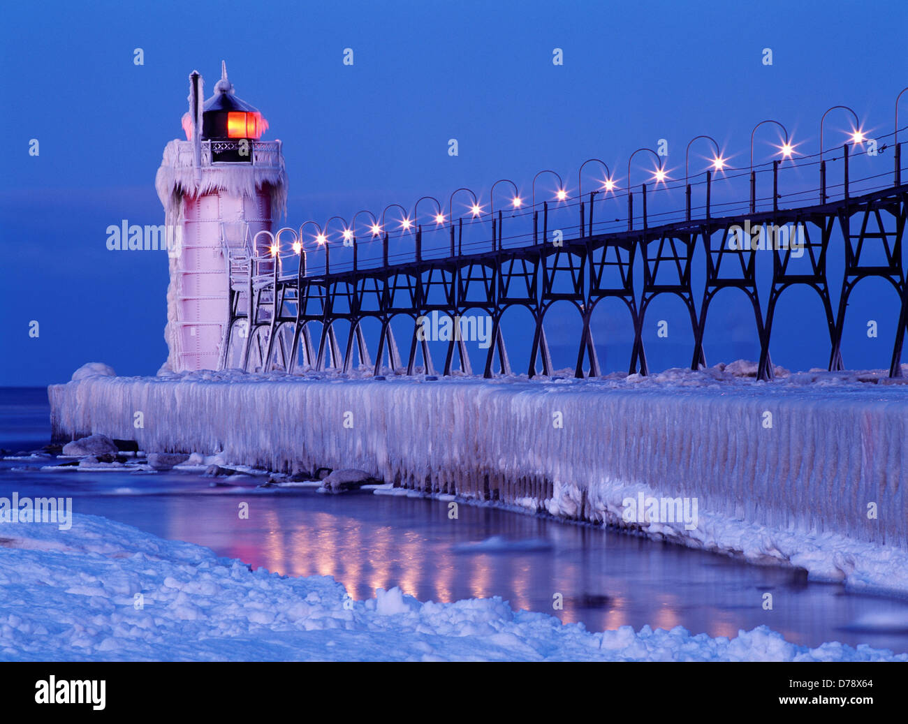 Ice-covered South Haven Pier Lighthouse illuminated at dawn mouth
