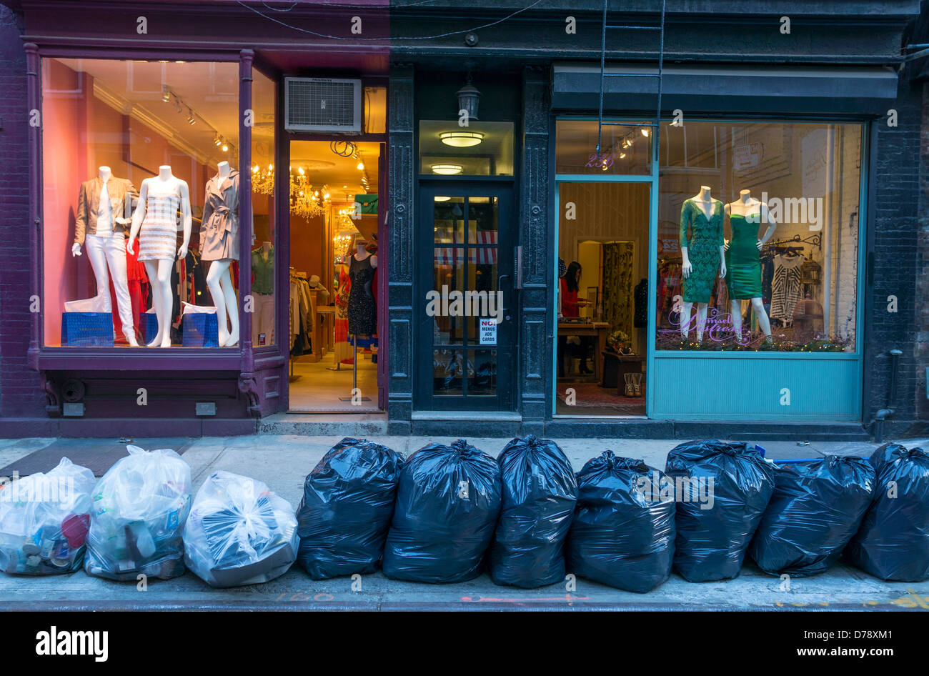 Two boutiques in Nolita with trash bags in front waiting to be collected, New York City - Stock Image