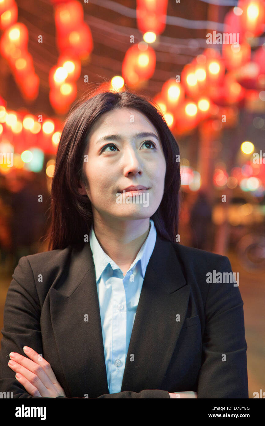 Businesswoman standing on the street, red lanterns on the background - Stock Image