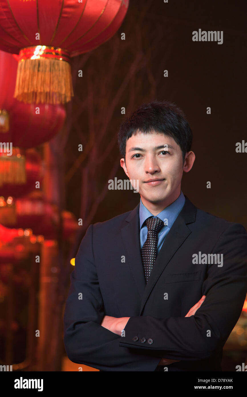 Businessman standing on the street, red lanterns on the background - Stock Image
