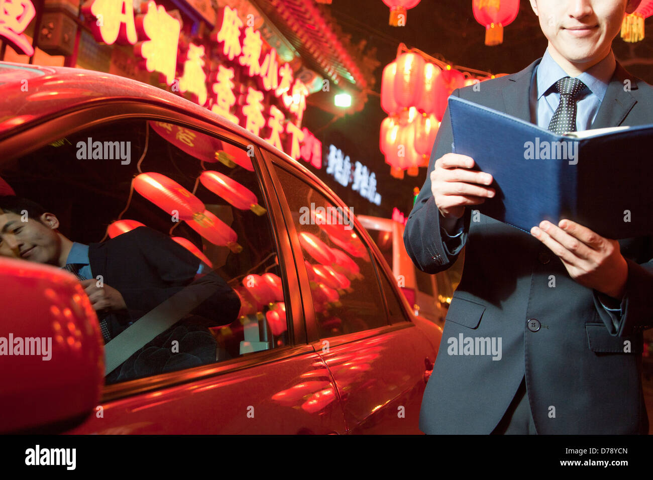 Businessman standing next to his car at night, Red lanterns on the background Stock Photo
