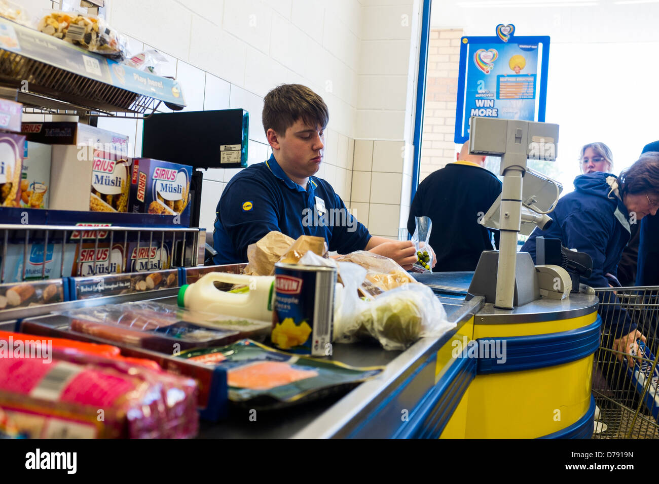 A young man working on the checkout at Lidl supermarket, UK - Stock Image