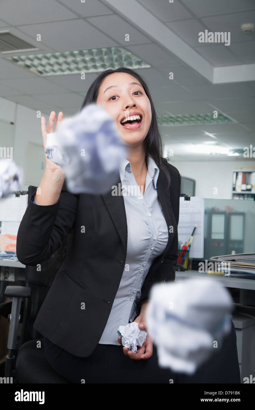 White-collar worker throwing paper in office - Stock Image