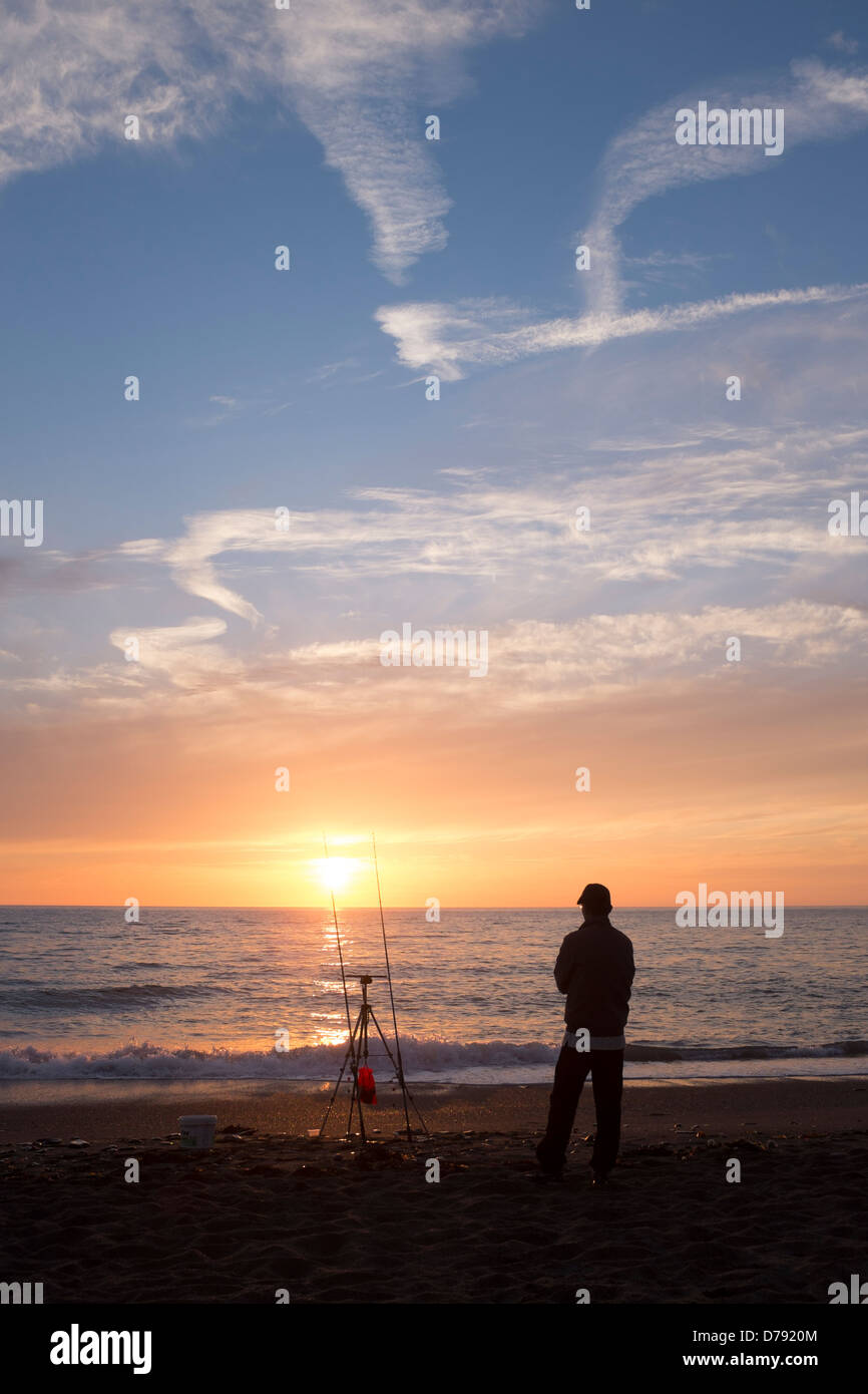 A lone fisherman watching the sunset, on the beach, Aberystwyth, Wales Uk April 23 2013 - Stock Image