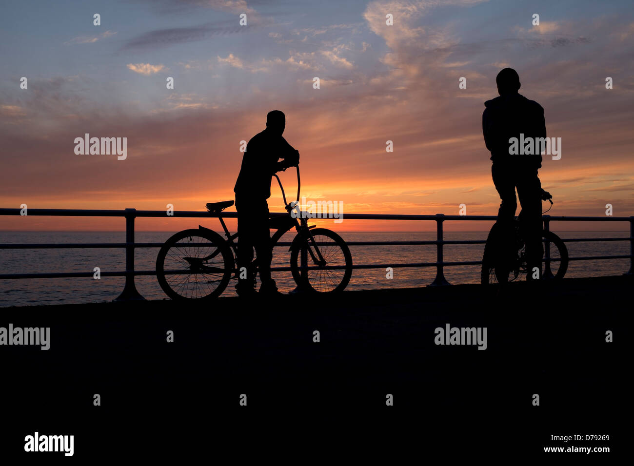Two cyclists in silhouette watching the sunset from the promenade, Aberystwyth, Wales Uk April 23 2013 - Stock Image