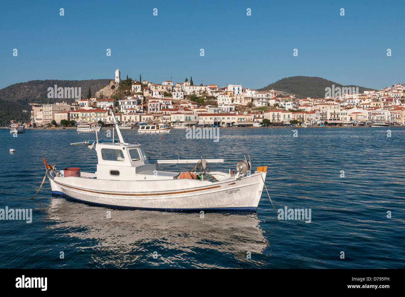 The Island and Town of Poros, seen from the harbour at Galatas, Attica, Peloponnese, Greece. - Stock Image