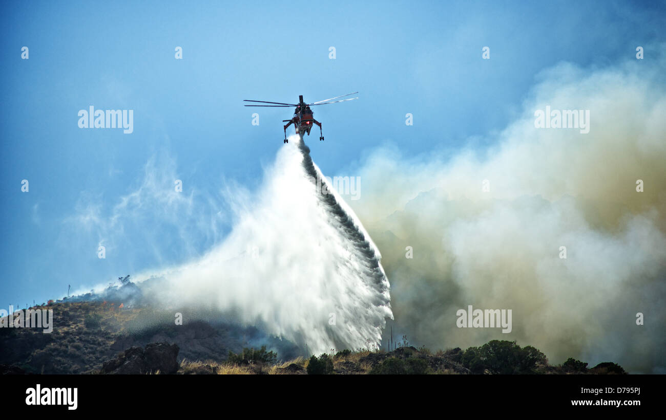 A firefighting helicopter douses a southern California wildfire north of Los Angeles. - Stock Image