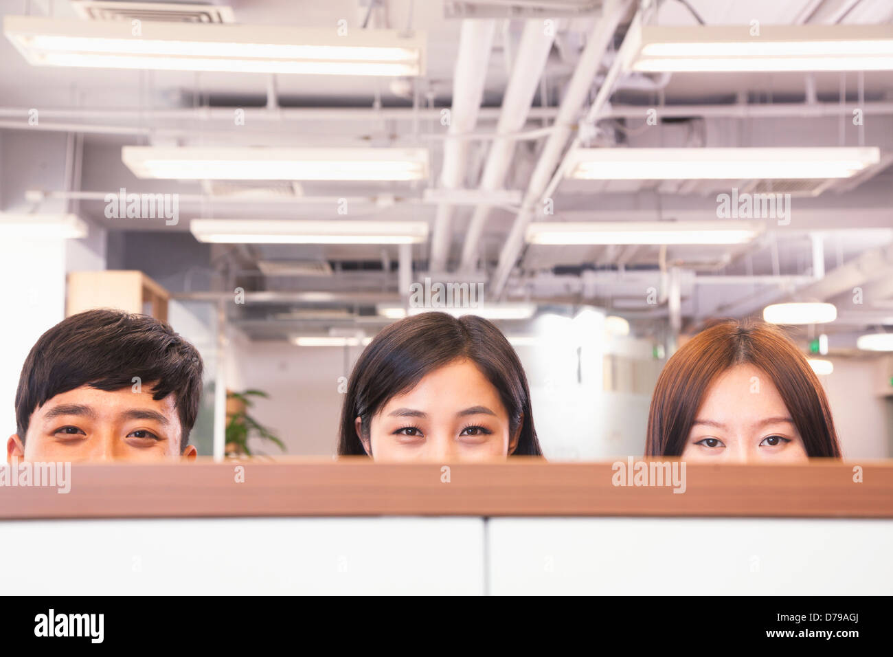 Office workers peeking over divider in office - Stock Image