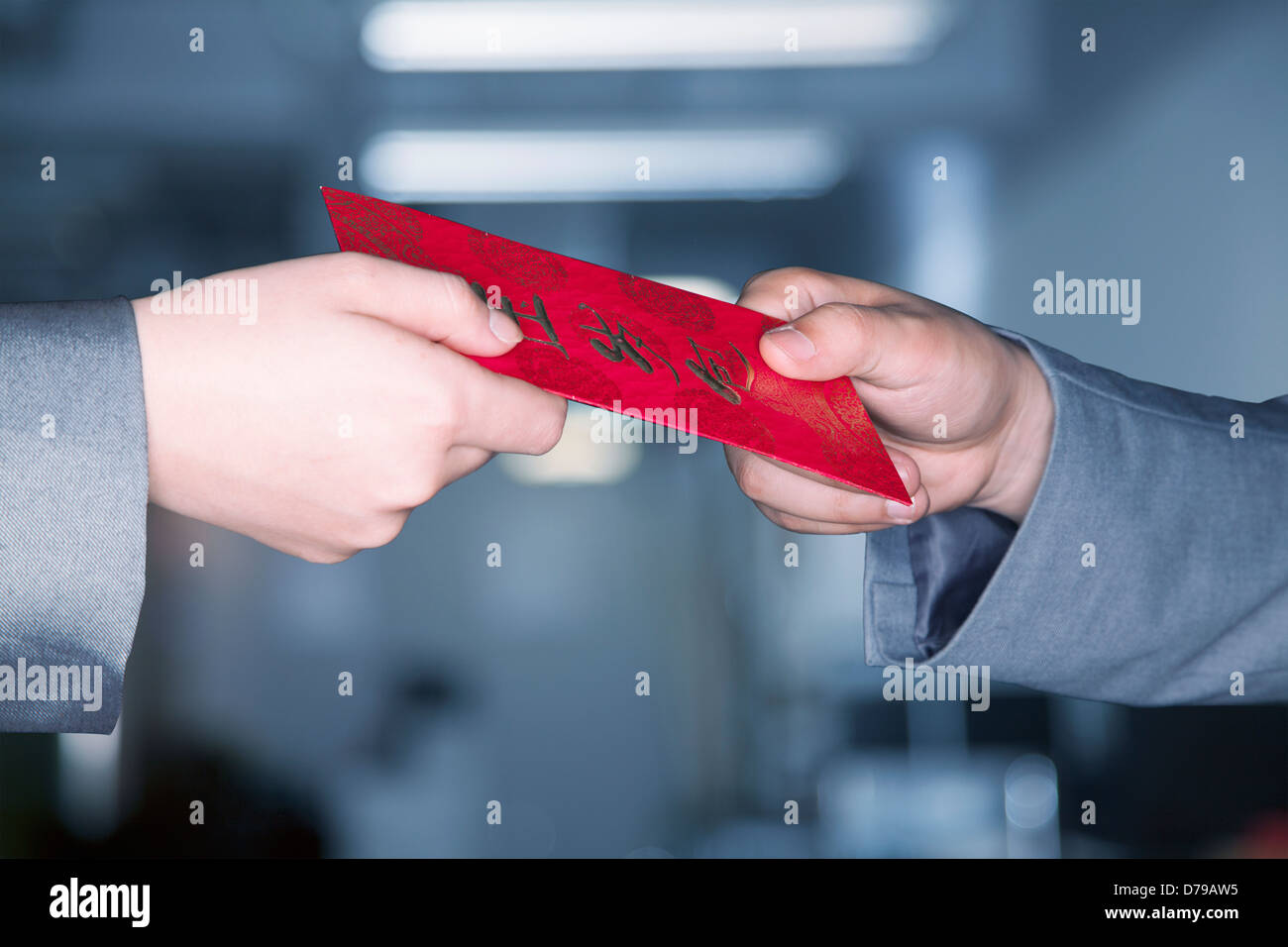 Close up on hands exchanging a red Chinese new years envelope - Stock Image