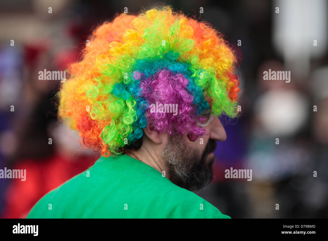 Man wearing a multi-colored wig. - Stock Image