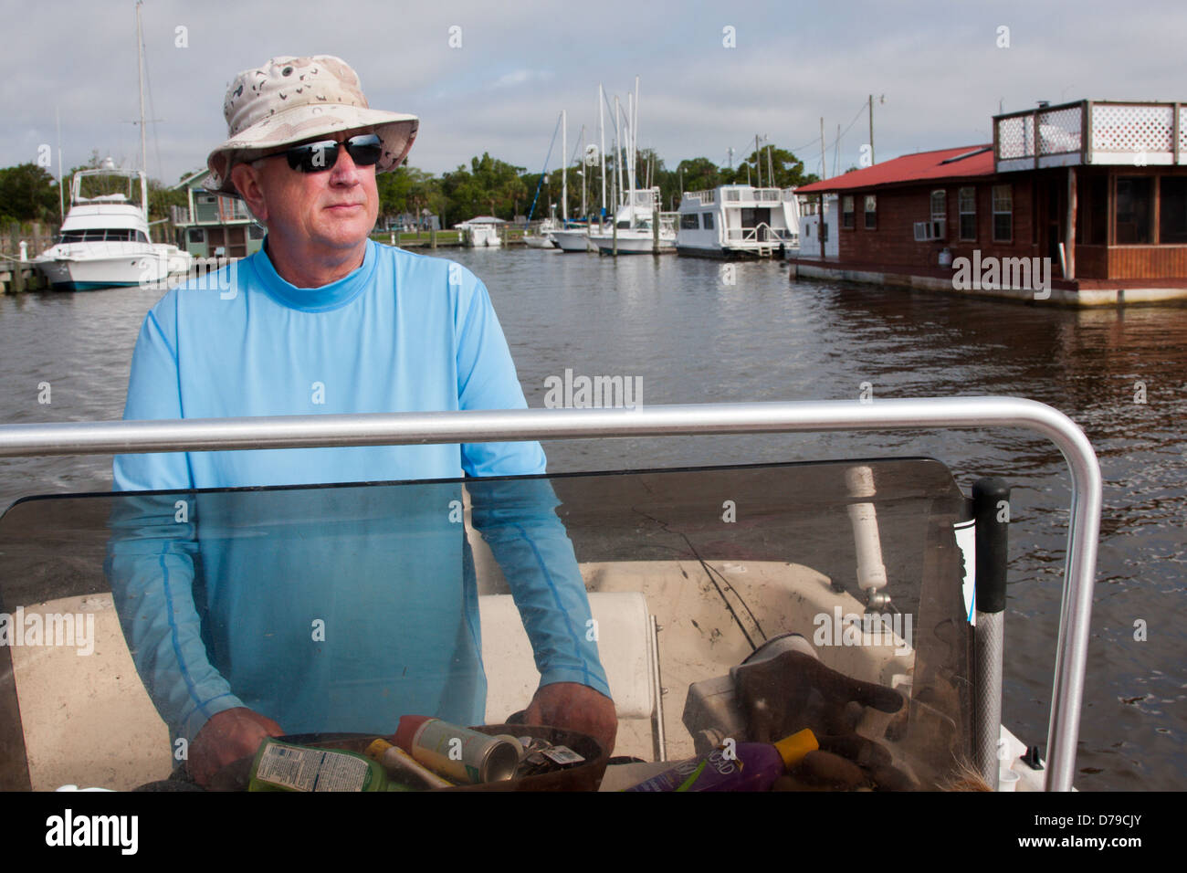 A man navigates a Carolina skiff out of the Battery Park harbor into Apalachicola bay, Florida, USA - Stock Image
