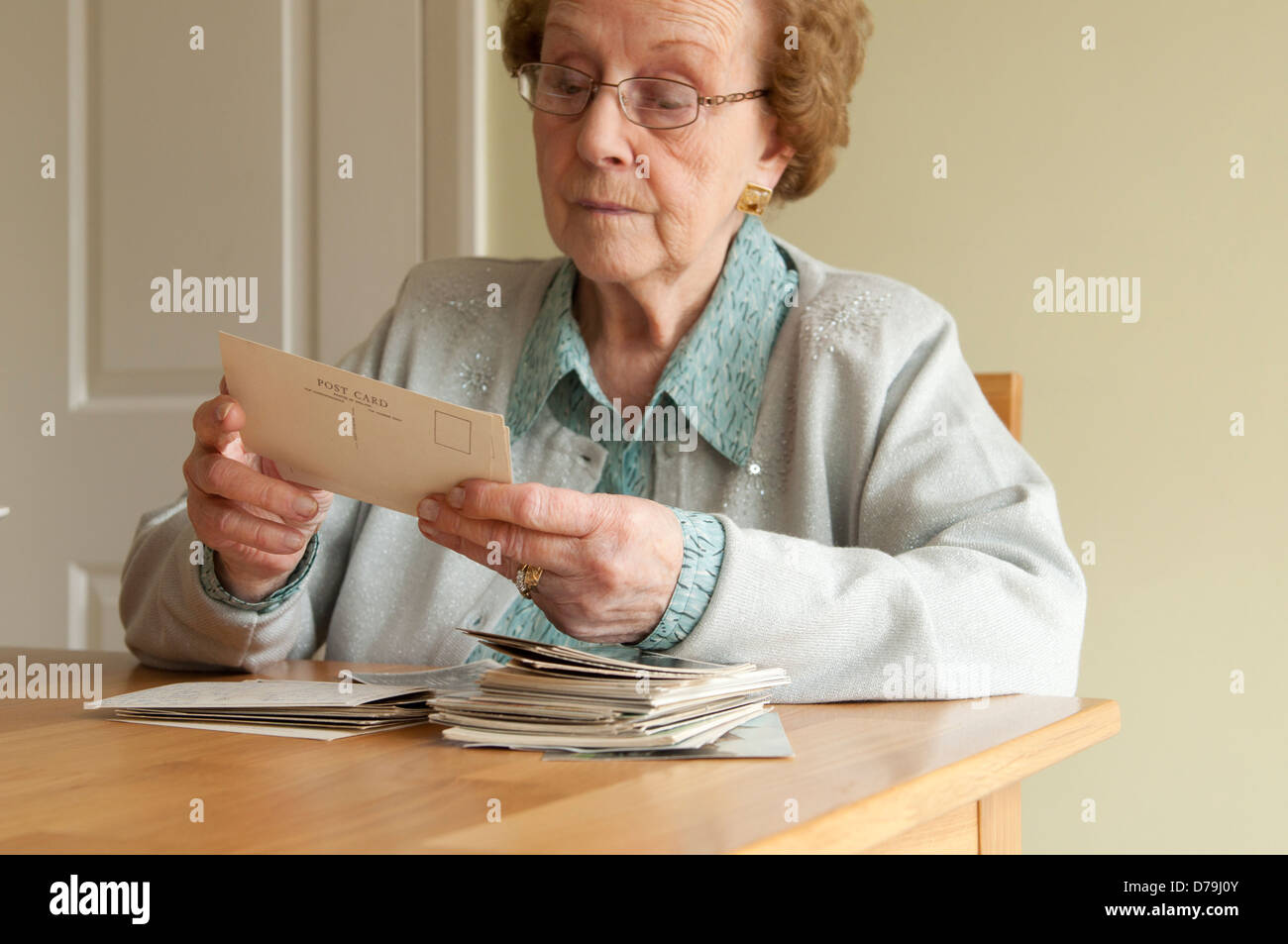 elderly woman looks at old postcards - Stock Image