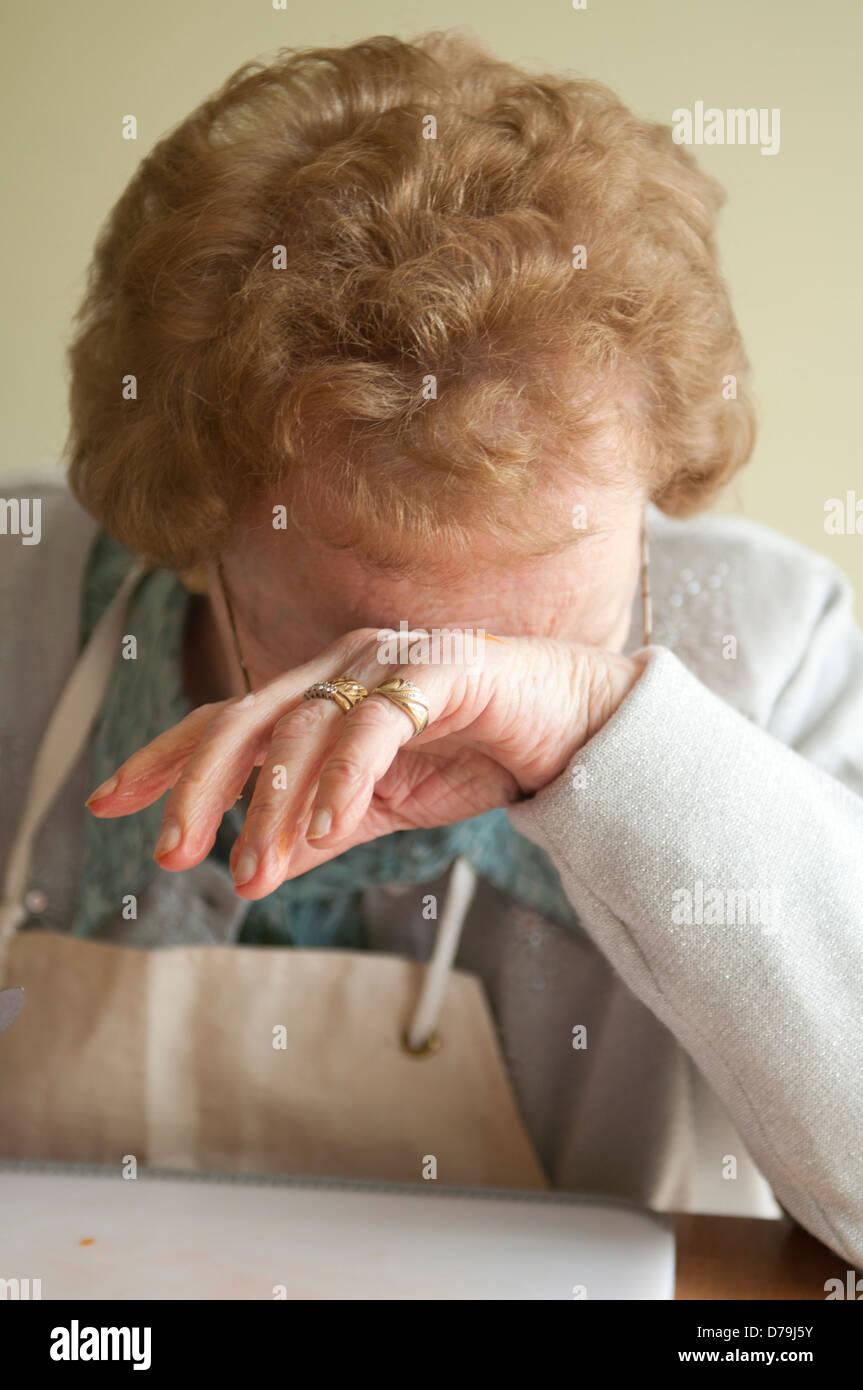 Elderly woman crying wearing apron - Stock Image