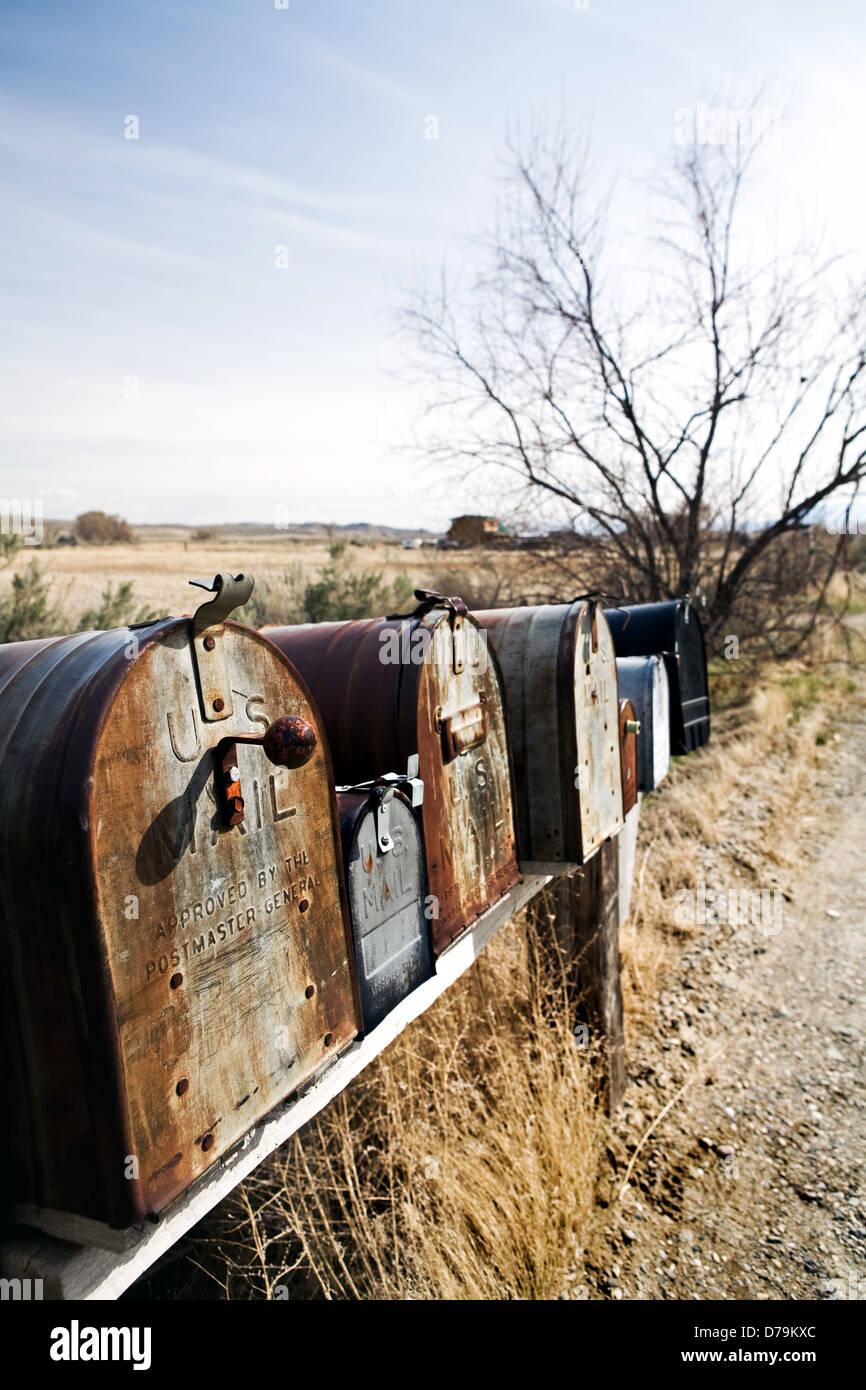 mailboxes in midwest United States, old vintage boxes in late sun rusting away - Stock Image
