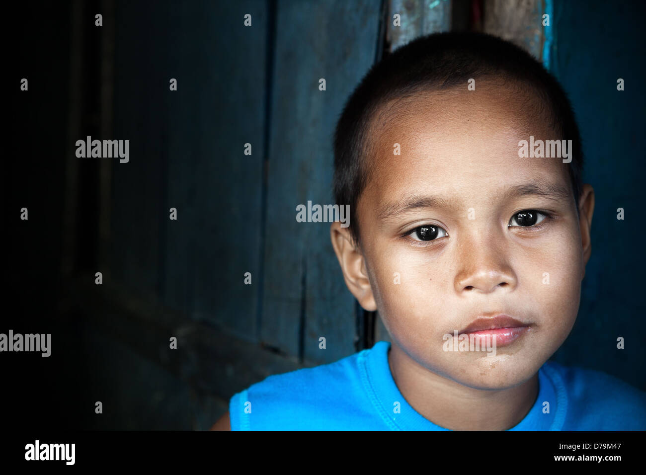 Portrait of an Asian child - Filipino boy by wall in natural light - Stock Image
