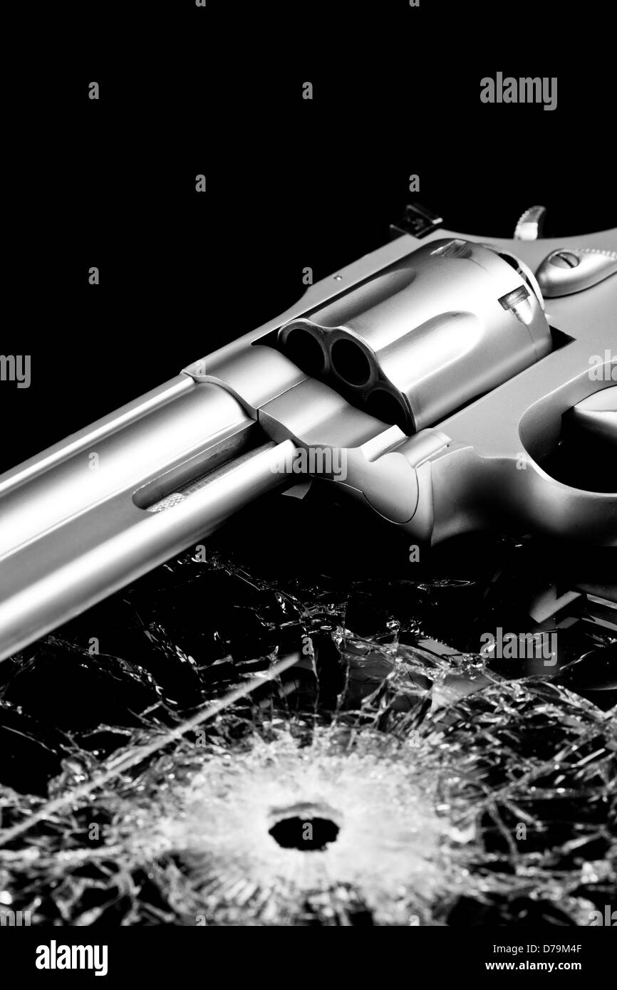handgun with bullet hole in glass isolated on black - modern revolver with broken glass - Stock Image