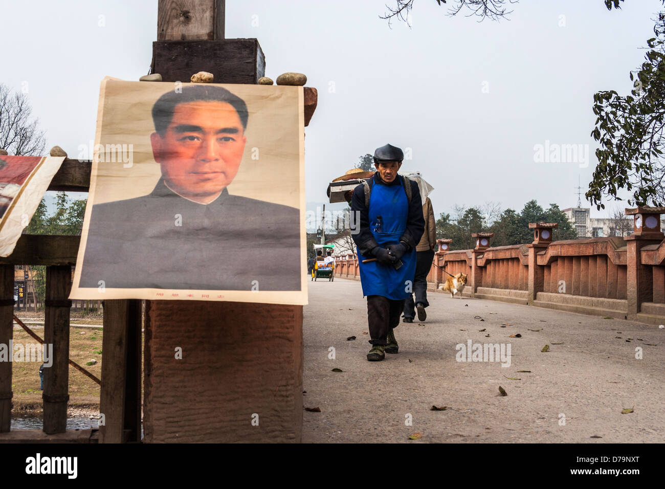 Chinese craftsman walking on a bridge with old Mao posters sold as souvenirs at Pingle village, near Chengdu, Sichuan, - Stock Image