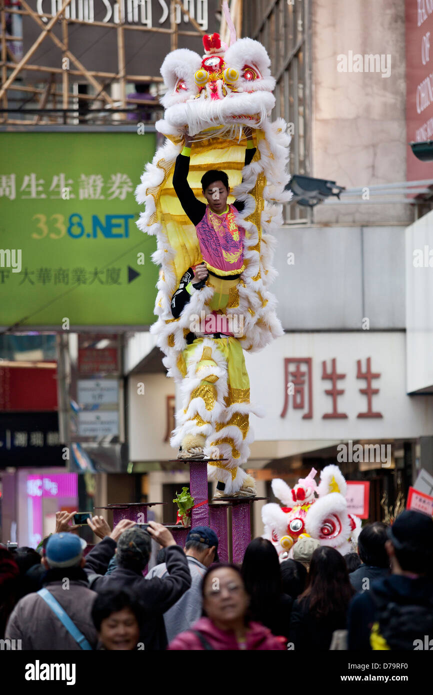 Lion dance on a busy street in Hong Kong - Stock Image