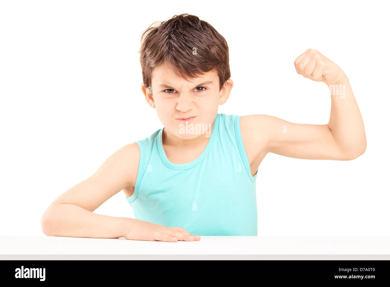 A mad child showing his muscles seated on a table isolated on white background - Stock Image