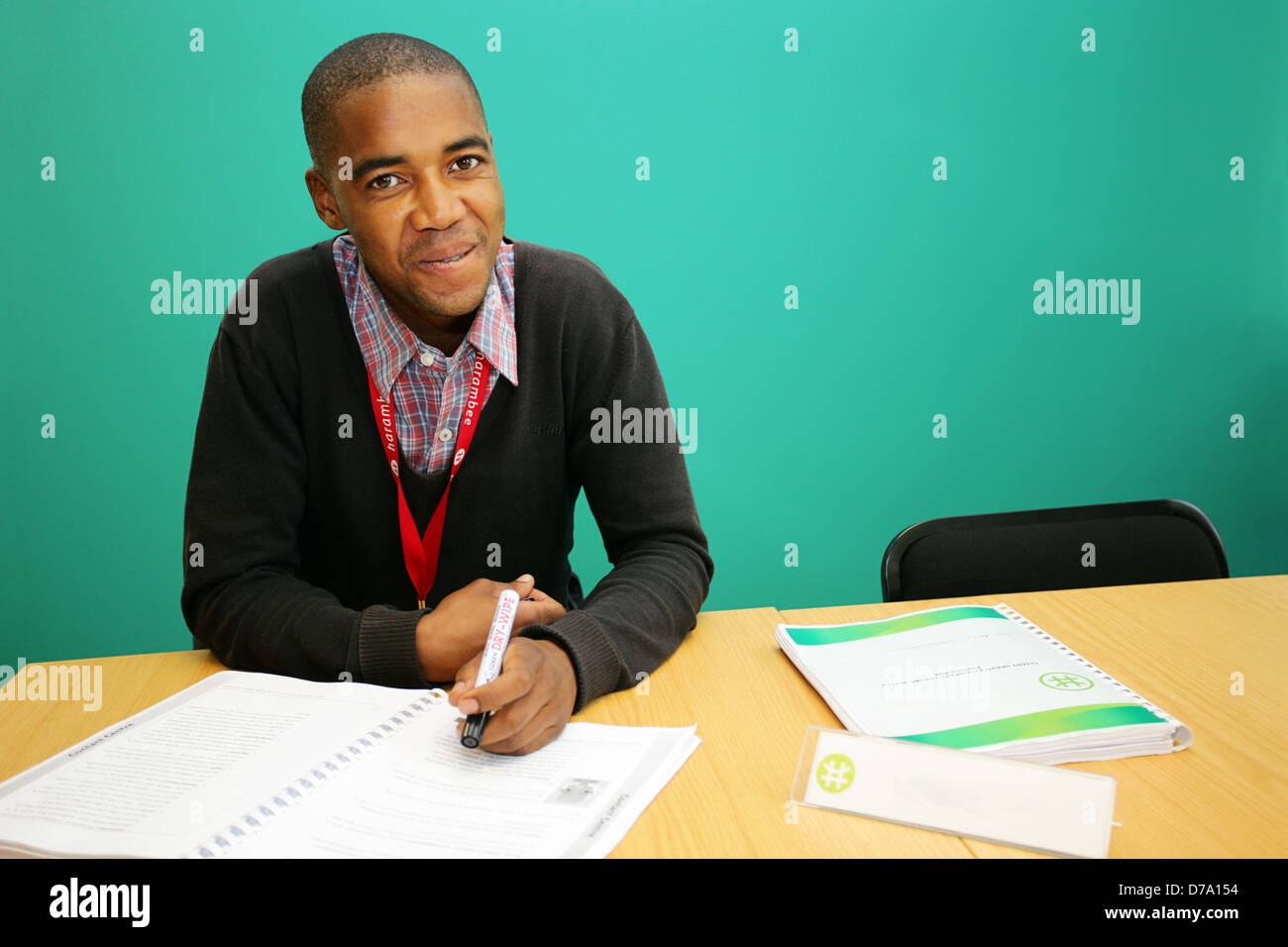 Cape Town based student training to be entry-level worker. Smiling in front of a plain green wall. - Stock Image