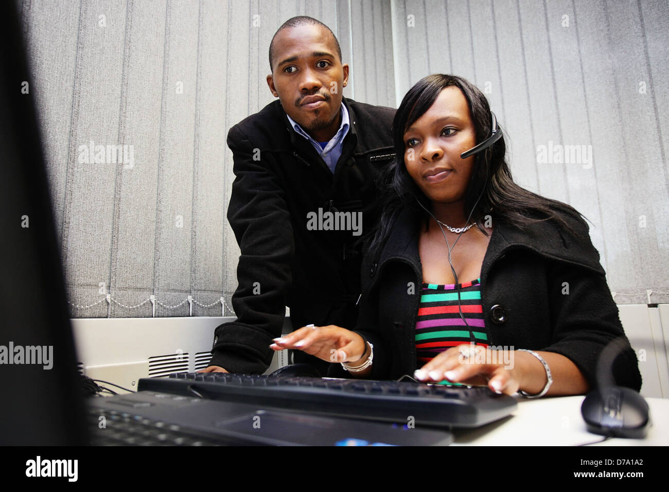Call center. Cape Town based students training at a computer to be entry-level workers. - Stock Image
