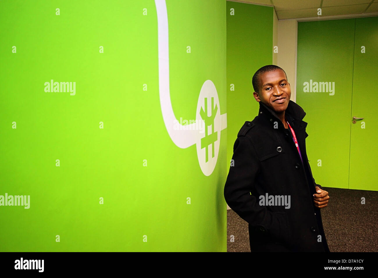 Cape Town based student training to be entry-level worker posing by a green wall - Stock Image