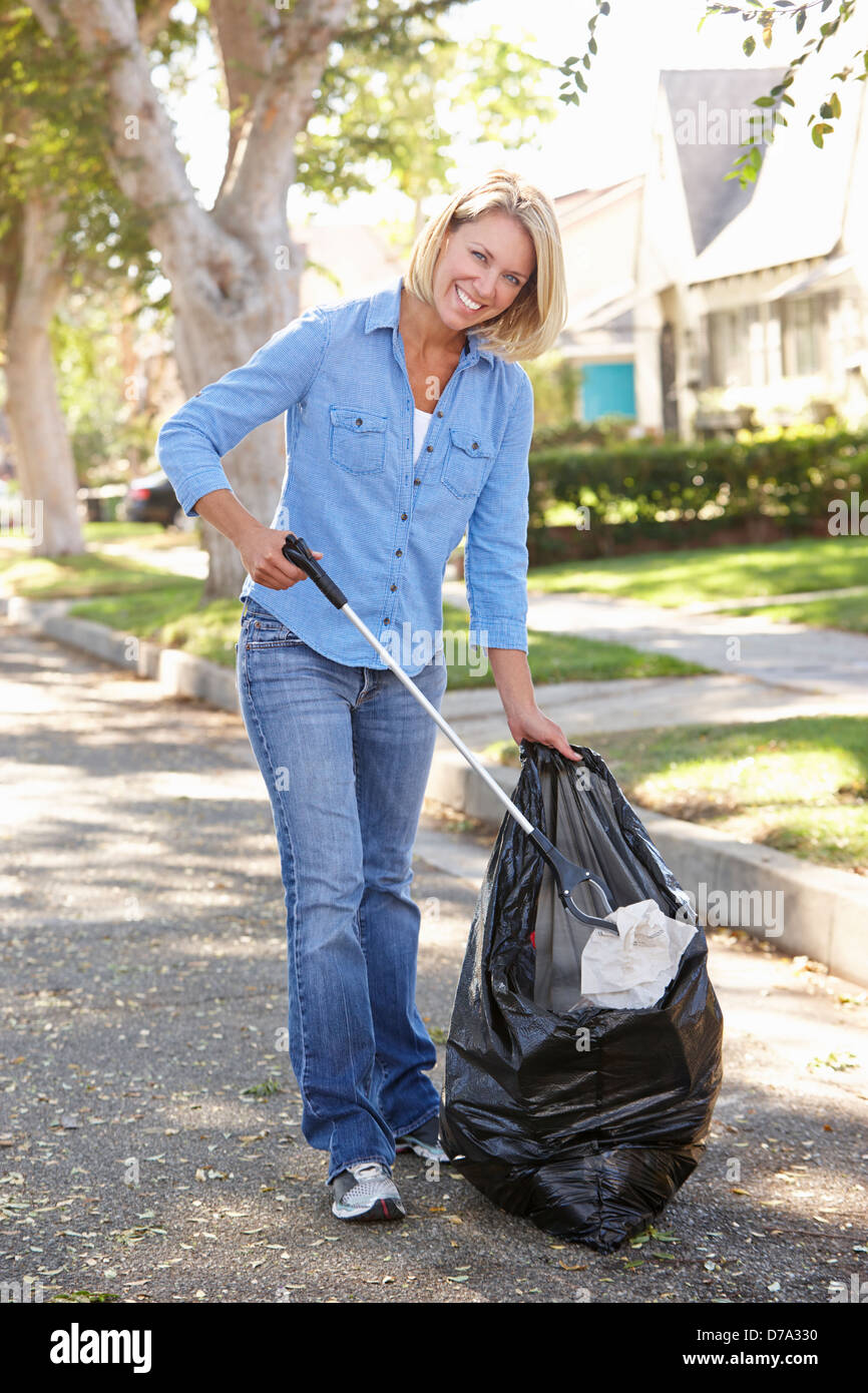 Woman Picking Up Litter In Suburban Street - Stock Image