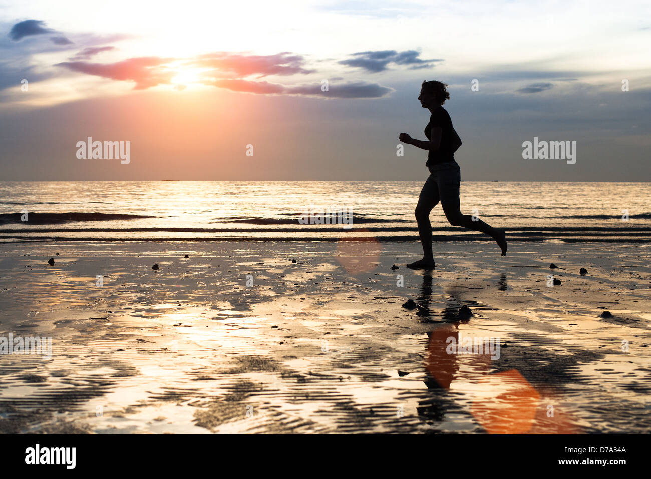 Silhouette of a young woman jogger at sunset on seashore. - Stock Image