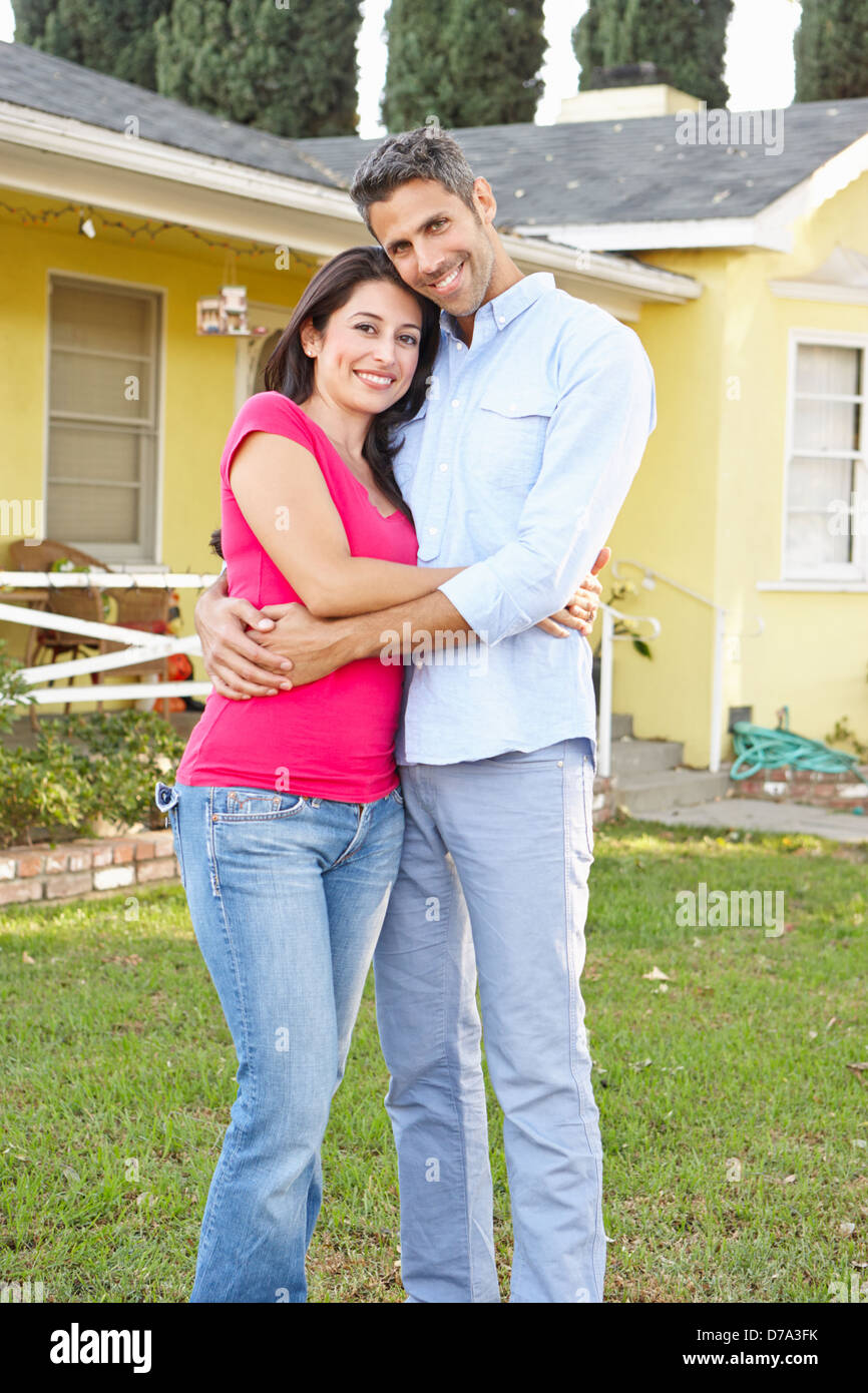 Couple Standing Outside Suburban Home - Stock Image