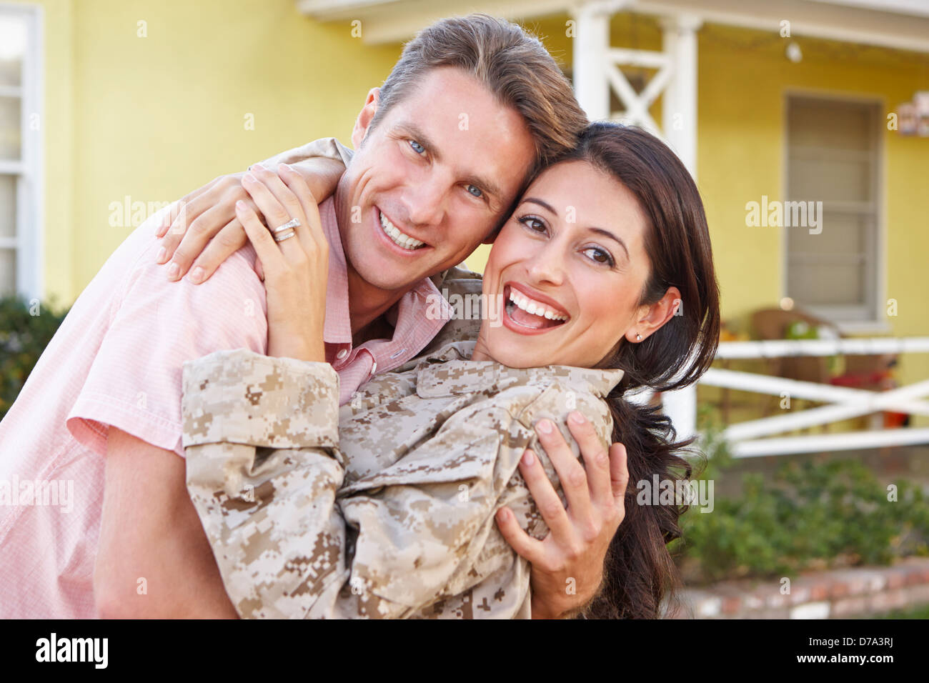 Husband Welcoming Wife Home On Army Leave - Stock Image