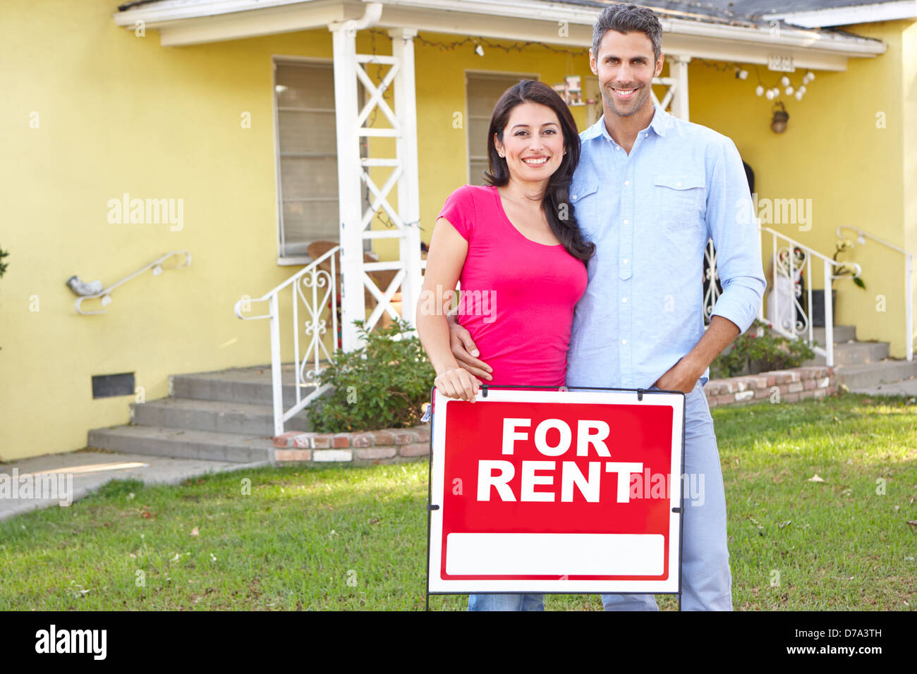 Couple Standing By For Rent Sign Outside Home - Stock Image