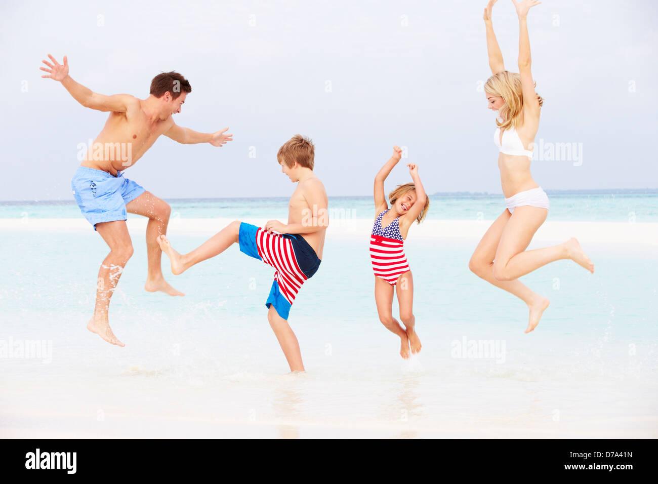 Family Having Fun In Sea On Beach Holiday - Stock Image