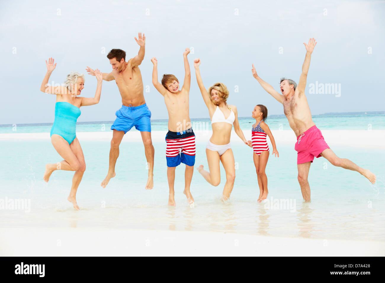 Multi Generation Family Having Fun In Sea On Beach Holiday Stock Photo