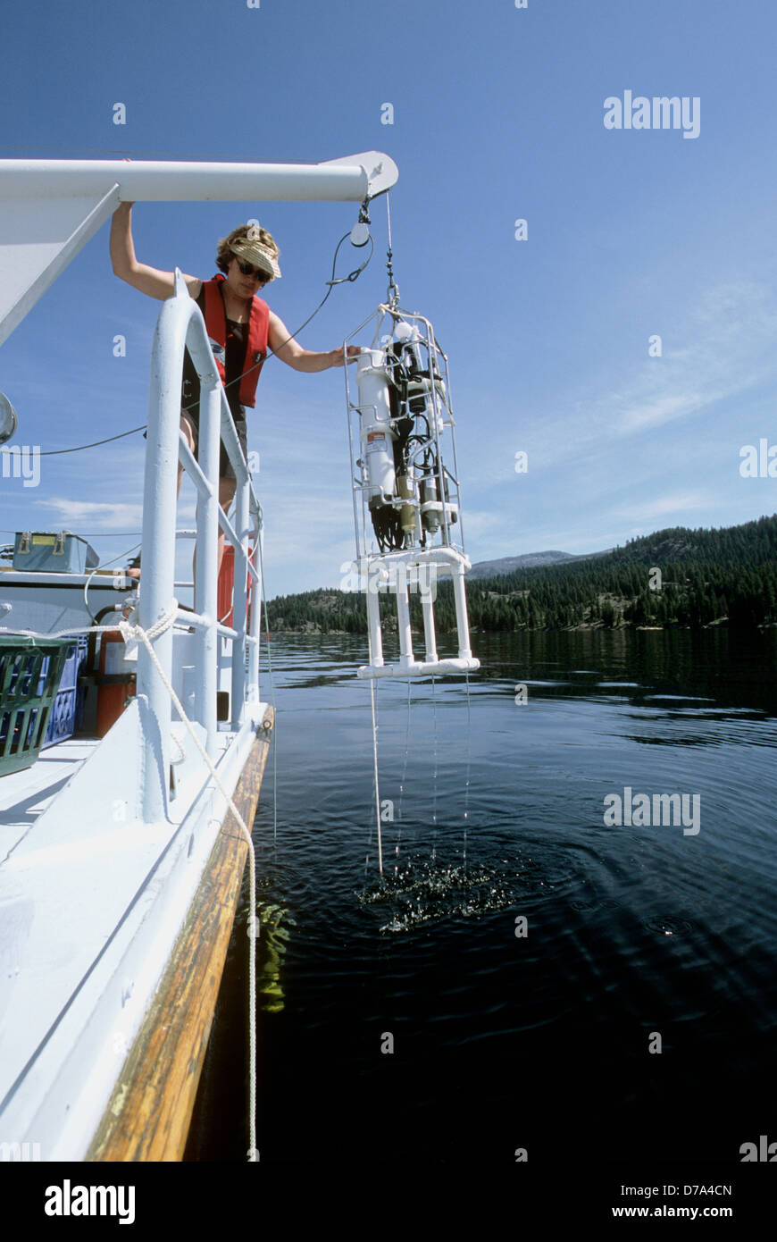 USGS hydrological technician deploying a multi-parameter water column profiler in Payette Lake in west-central Idaho. - Stock Image