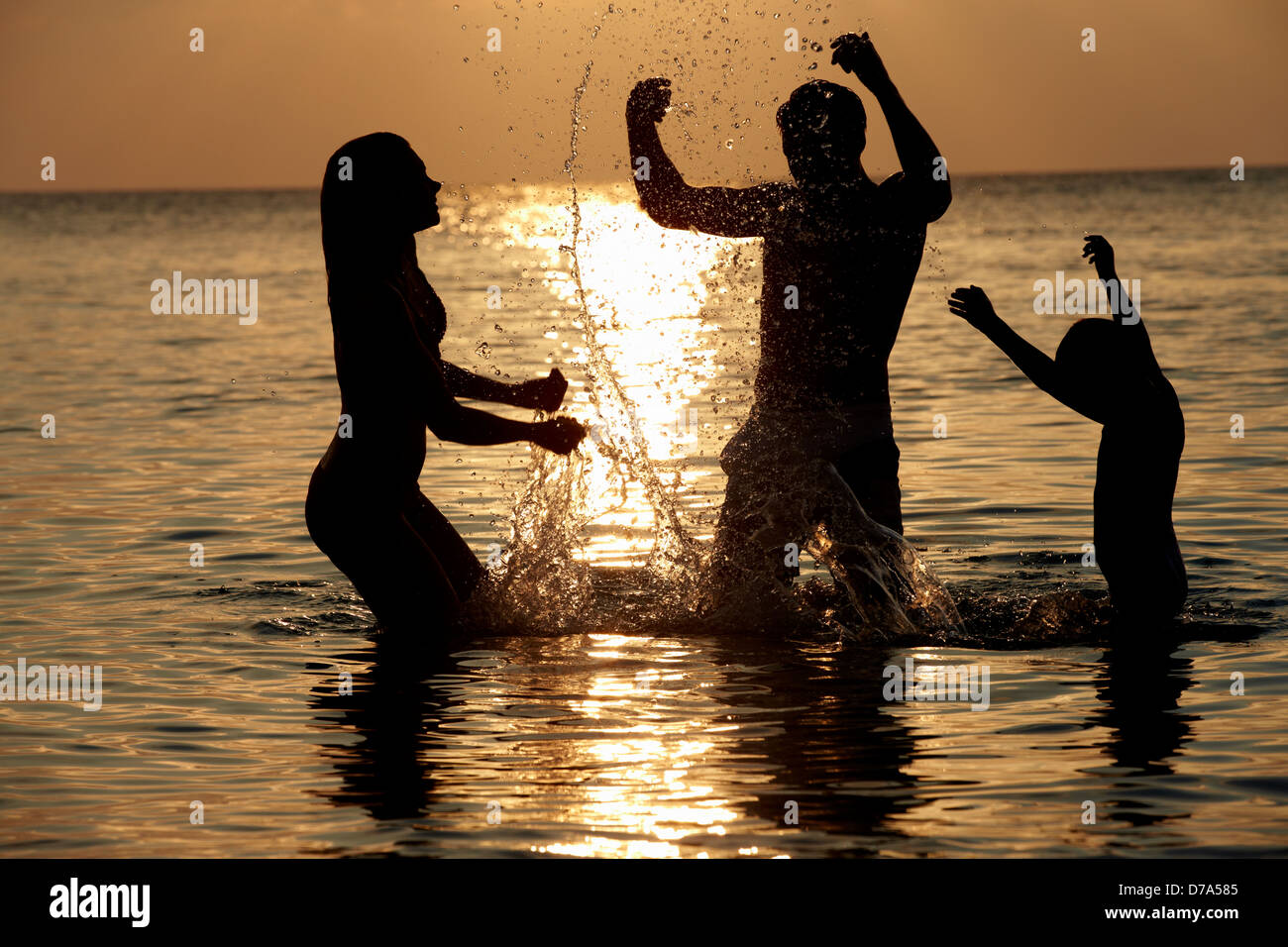Silhouette Of Family Having Fun In Sea On Beach Holiday - Stock Image