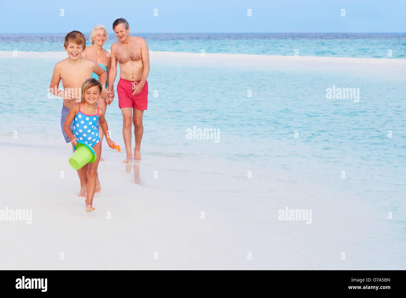 Grandparents And Grandchildren Having Fun On Beach Holiday Stock Photo