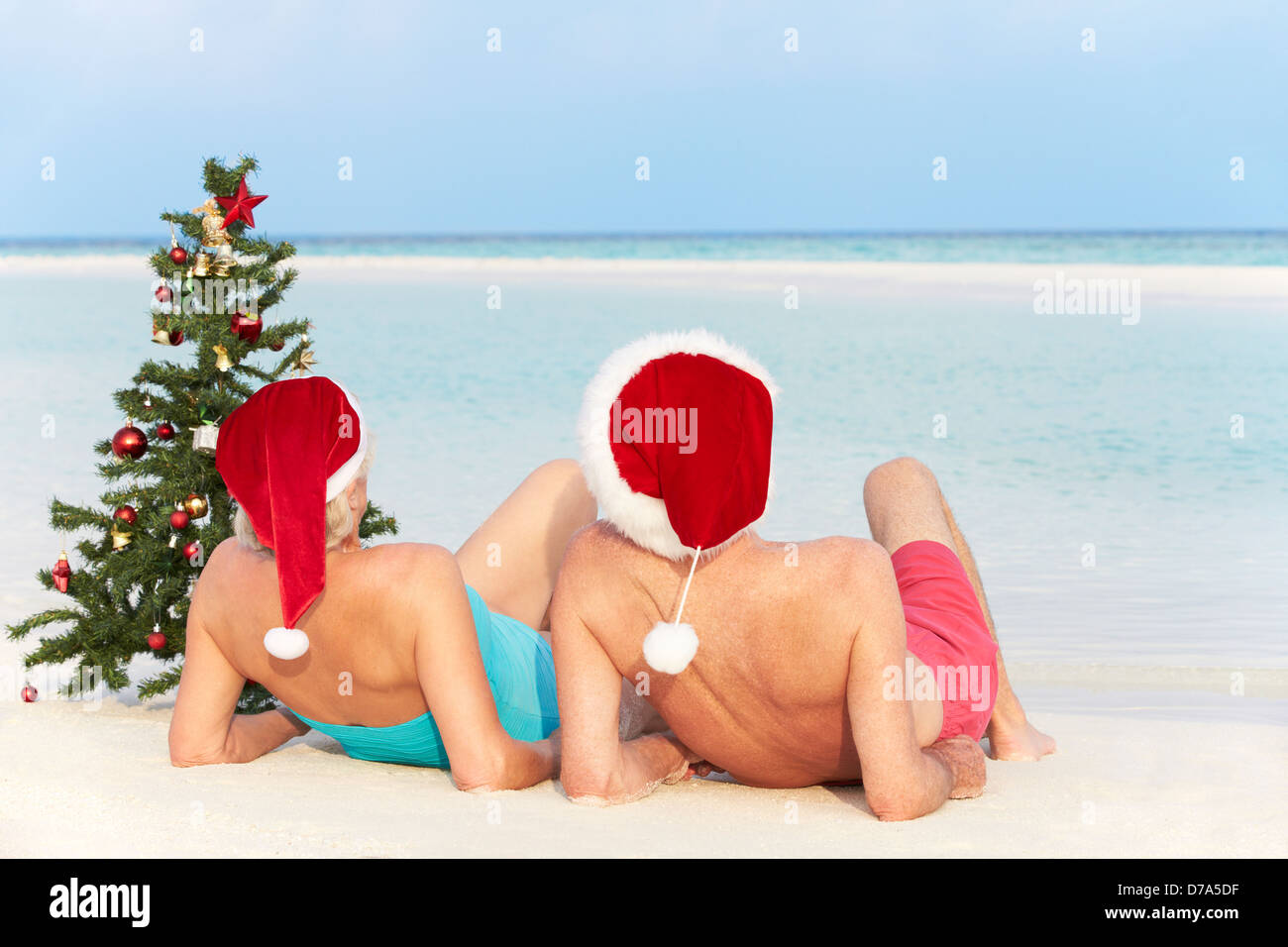 Senior Couple Sitting On Beach With Christmas Tree And Hats - Stock Image