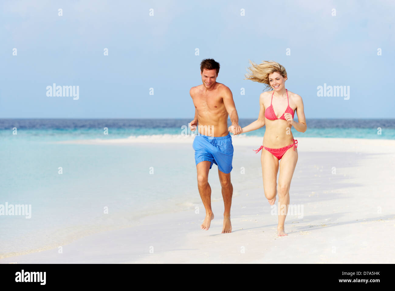 Romantic Couple Running On Beautiful Tropical Beach - Stock Image