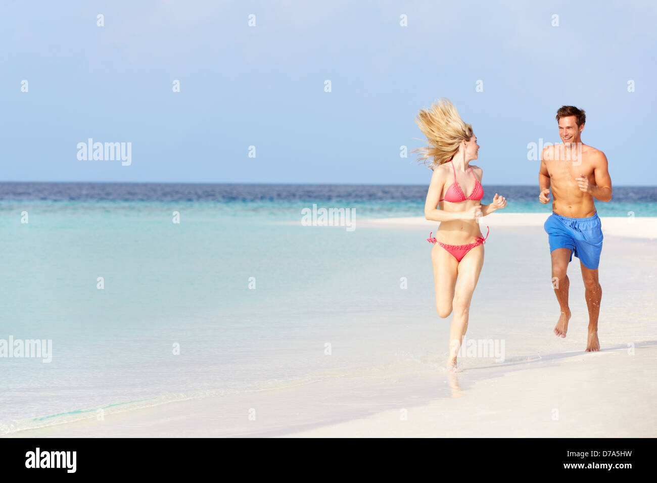 Romantic Couple Running On Beautiful Tropical Beach - Stock Image