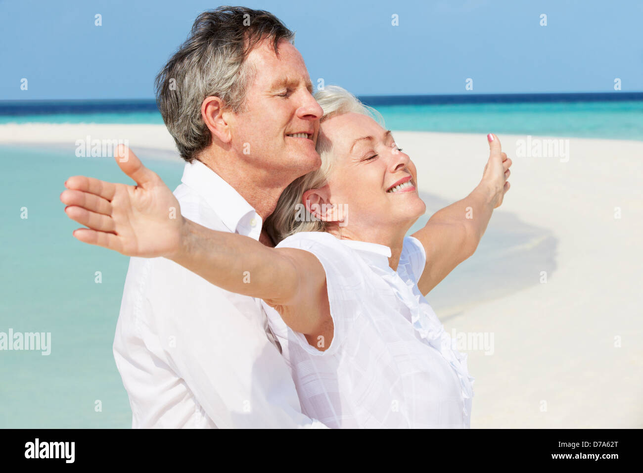 Senior Couple Withs Arms Outstretched On Beautiful Beach - Stock Image