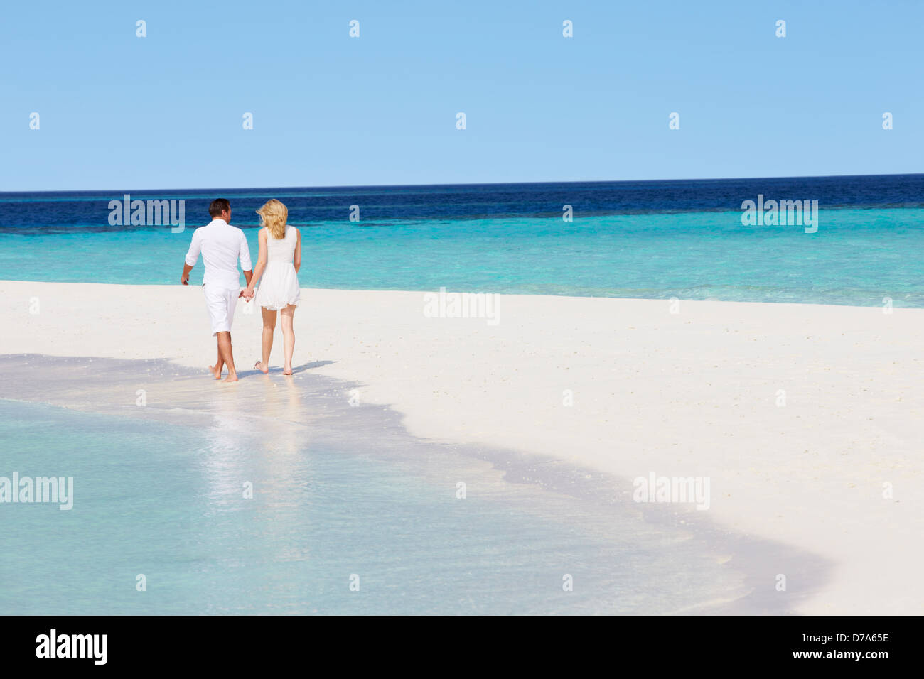 Rear View Of Romantic Couple Walking On Tropical Beach Stock Photo