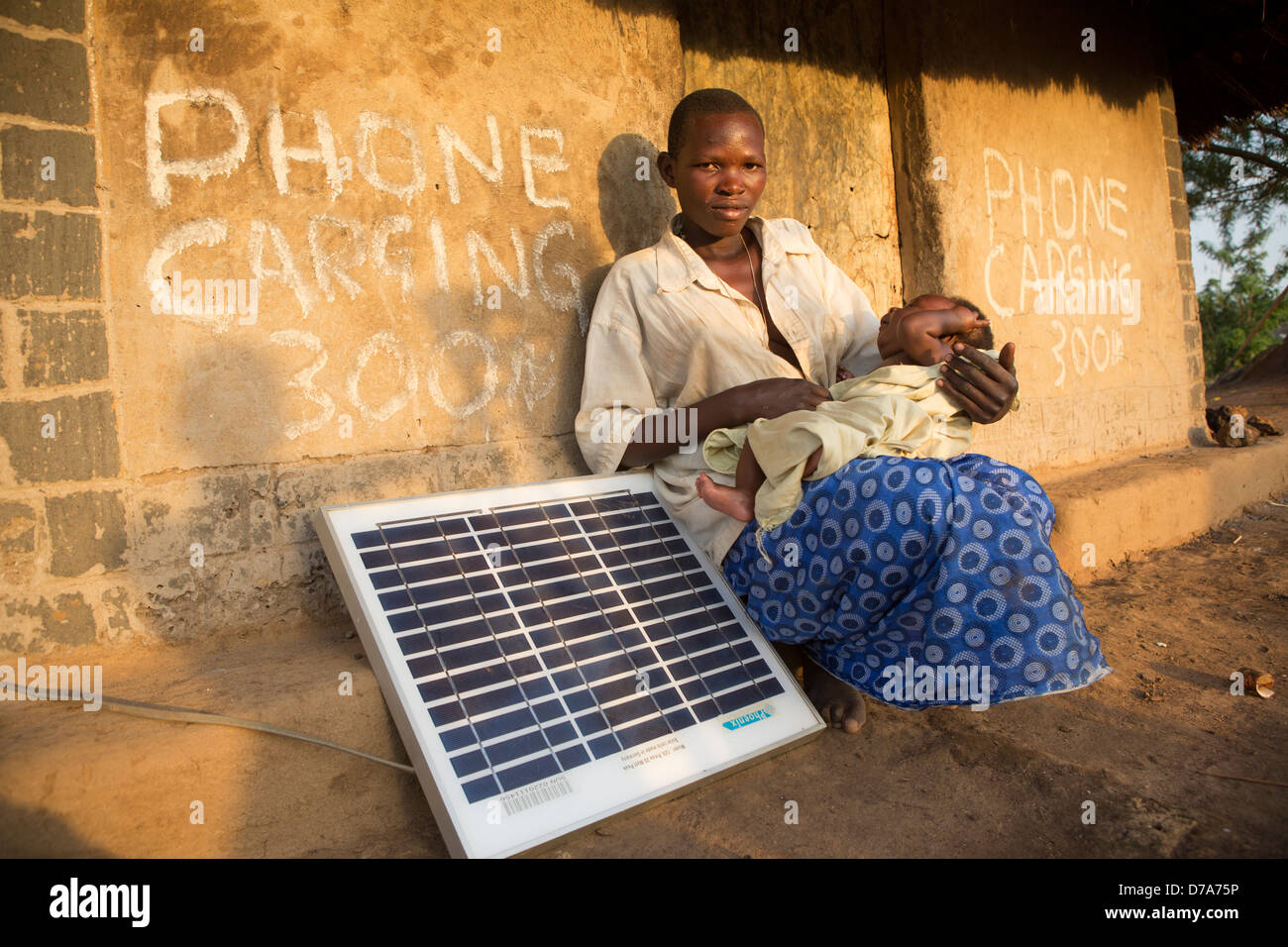 Mother with a solar panel in Lira District, Uganda, East Africa. Stock Photo