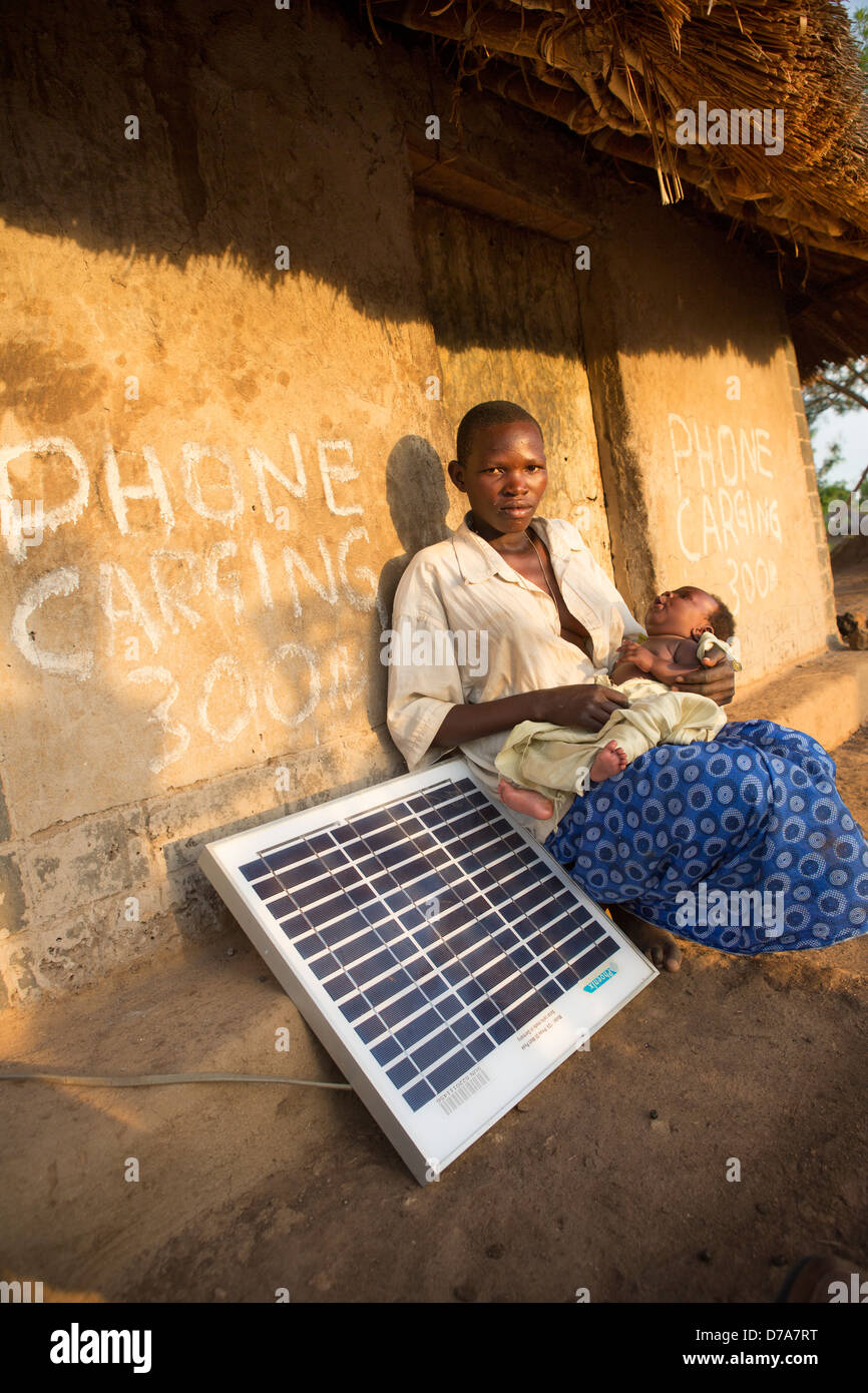 Mother with a solar panel in Lira District, Uganda, East Africa. - Stock Image