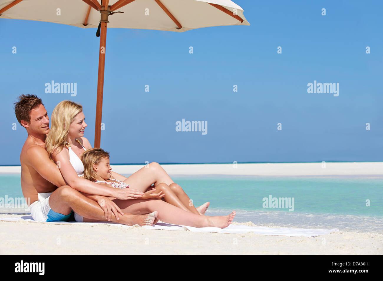 Family Sitting Under Umbrella On Beach Holiday - Stock Image