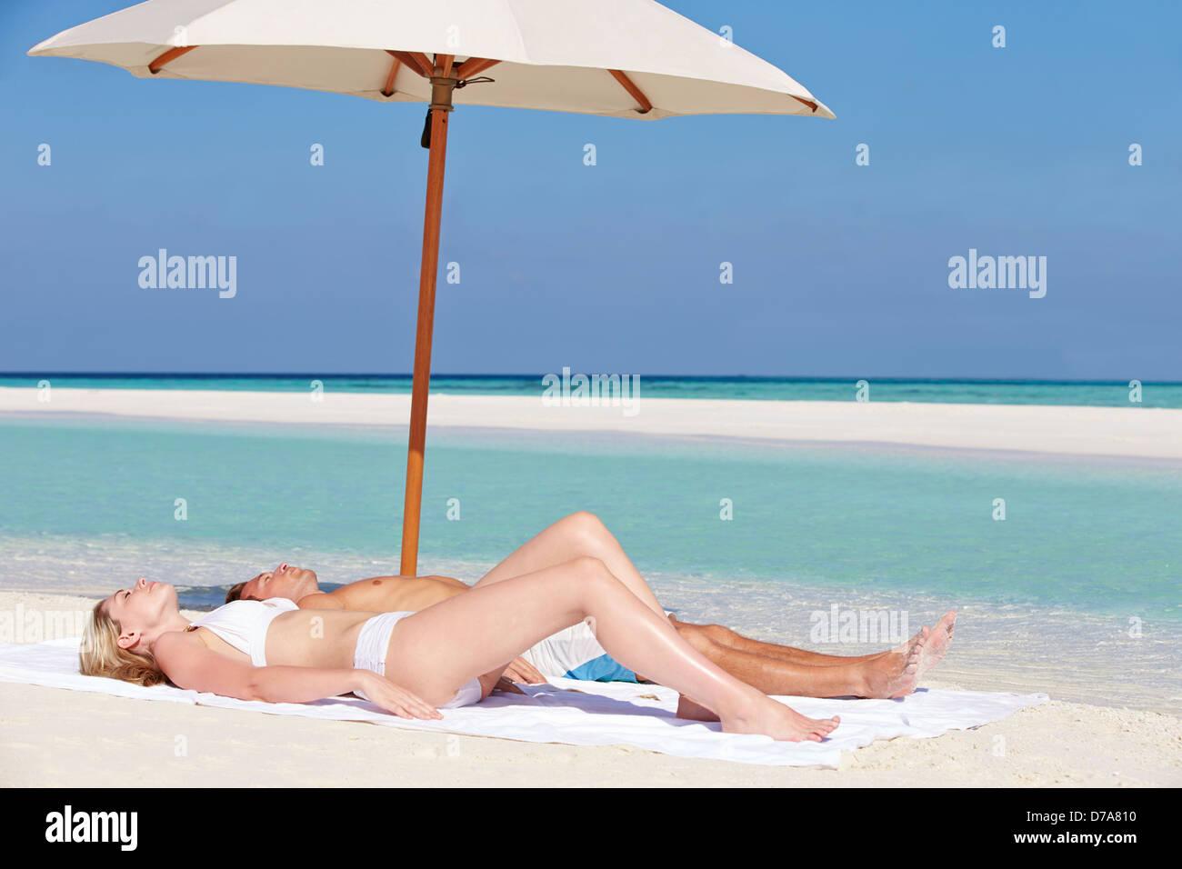 Couple Sunbathing On Beautiful Beach Holiday - Stock Image